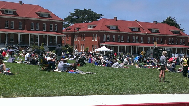 A large group of people relaxing on the Presidio main lawn at which a disaster preparedness event was held