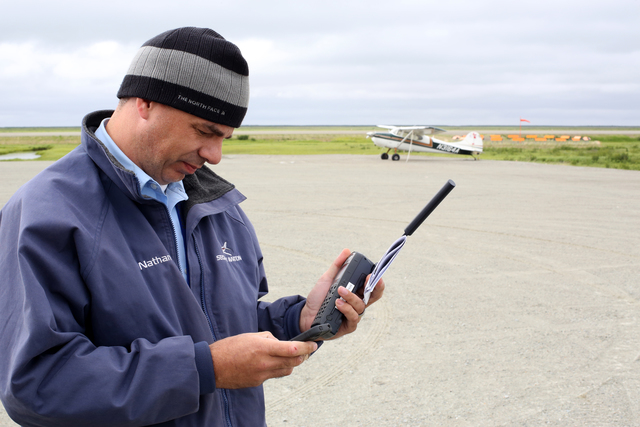 Alakanuk, Alaska, July 16, 2013 -- Security Air pilot Nathan Semler calls flight control via satelitte phone in the remote western Yukon territory for clearance to take off of this gravel airstrip. FEMA is responding per the invite of the Governor with teams to work with the State of Alaska and the disaster survivors.  Adam DuBrowa/ FEMA
