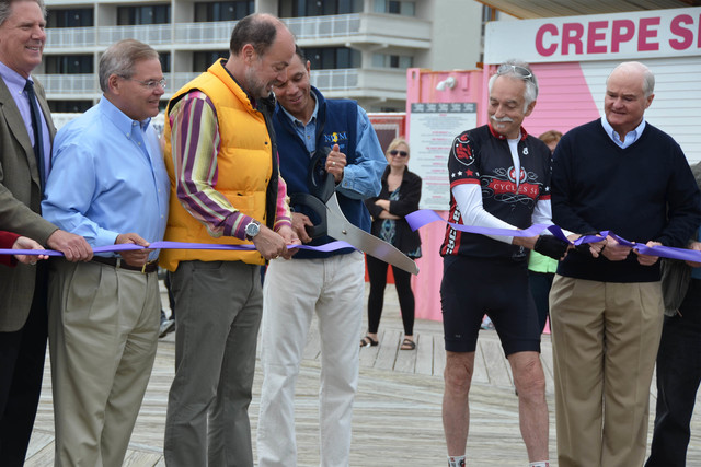 Asbury Park, N.J., May 18, 2013 -- A snip of a purple ribbon by Asbury Park's Mayor Ed Johnson (center) signifies the completion of repair and reconstruction of the city's boardwalk, which was damaged by Hurricane Sandy last October. Mayor Johnson is joined, from left to right, by Congressman Frank Pallone Jr., Senator Robert Menendez, Deputy Mayor Don Loffredo, City Manager Terry Reidy and Freeholder John P. Curley. FEMA's Public Assistance grant program provided a portion of the funds for the project in addition to donations from local businesses and state and local sources.   Photo by Sharon Karr/FEMA