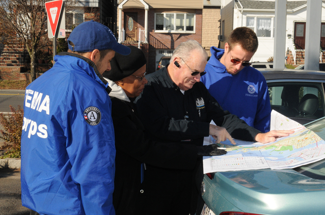 Bayonne, N.J., Nov. 26, 2012 -- This FEMA Community Relations (CR) Outreach Team (FEMA CR Team Lead Mike Dunn, FEMA CR Specialist Juanita Manley, FEMA Corps members Dane Gelllerup and Saul Korzenecki) refer to a map in preparation for their door-to-door outreach to Hurricane Sandy survivors. FEMA is here to help individuals and the community recover from this record breaking storm.  George Armstrong/FEMA
