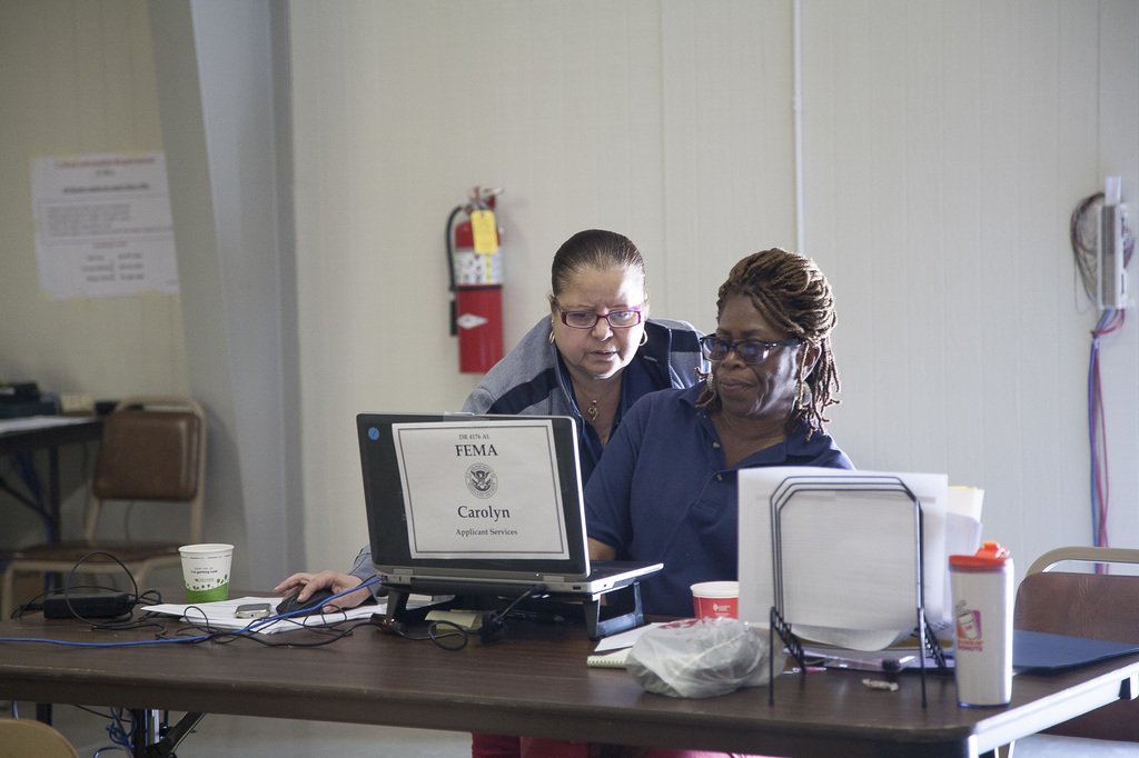 Bessemer, Ala., May 23, 2014 -- Oracylis  Perez-Cosme (standing) confers with fellow specialist Carolyn Gordon about disaster recovery issues. Ed Edahl/FEMA
