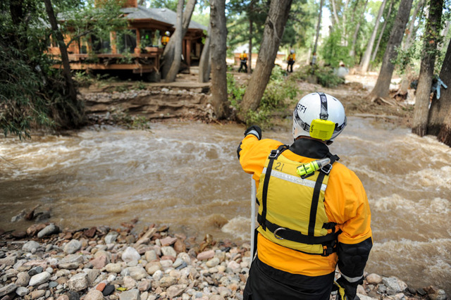 Boulder, Colorado September 17, 2013 -- FEMA's Urban Search and Rescue (US&R) NE-TF1 safety officer watches as the team conduct a search of a home now in the river at the mouth of Left Hand Canyon.  Photo: Michael Rieger/FEMA