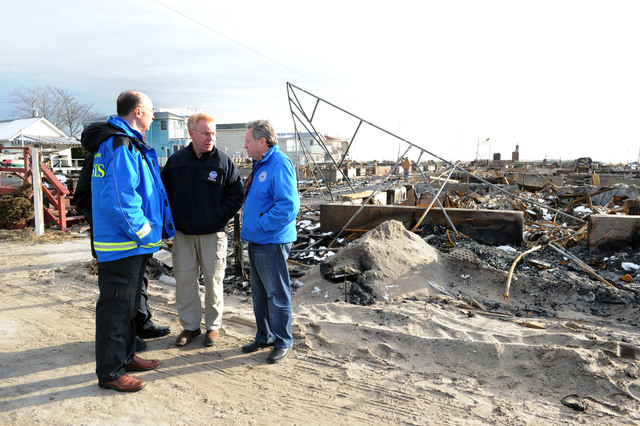 Breezy Point, N.Y., Nov. 8, 2012 --FEMA Federal Coordination Officer Mike Byrne, center, New York Commissioner of Homeland Security and Emergency Services Jerome Hauer, left,  and Robert Ungar, right visit an area where over a hundred houses were destroyed from a fire that started during Hurricane Sandy.  Jocelyn Augustino/FEMA