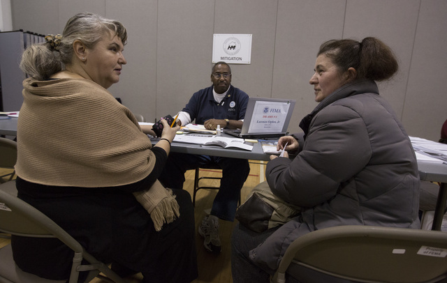 Brooklyn, N.Y., Dec. 7, 2012 -- Marine Aphkhazava (left) interprets Georgian for Mzia Gogua (right) to Lorenzo Ogden, Jr. FEMA Hazard Mitigation Specialist, Community Education and Outreach (center) under a program in which FEMA brings in interpreters to assist non- English speakers affected by Hurricane Sandy at DRC# 51 in Brooklyn, NY, December 7, 2012. FEMA is working with various partners including federal, state local and tribal governments, voluntary faith-based and community-based organizations, along with the private sector, to assist residents impacted by Hurricane Sandy. Chris Kleponis/ FEMA