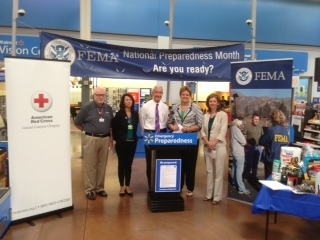 Chandler, Ariz., Sep. 4, 2013 --- Walmart partners with FEMA and local emergency management organizations to kick off the official September 1 start of National Preparedness Month from a Walmart store in Chandler. FEMA Region 9 Administrator Nancy Ward (fourth from left)  poses for photos with, from left to right, Randy Weddle, Chief Executive Officer of the Grand Canyon Chapter of the American Red Cross; Christina Raasch, Walmart Market Manager;  Chandler Vice Mayor Jack Sellers; and Wendy Smith-Reeve, Director of the Arizona Division of Emergency Management. Photo by Michael Cummings/FEMA