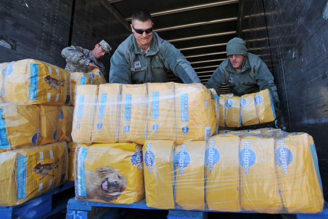 Charleston, W.Va., Nov. 6, 2012 -- Members of West Virginia's Army and Air National Guard work together to unload a truck full of donated Pedigree dog food at Yeager Airport. The pet food will be distributed in areas of the state hard hit by Hurricane Sandy and the aftermath that dumped several feet of snow, caused heavy rain, and brought high winds to the area. FEMA is coordinating the delivery of food and other commodities in West Virginia with federal, state, and local partners. Norman Lenburg/FEMA