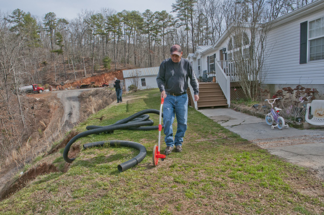 Cherokee, N.C., March 20, 2013 -- Denny Ensley, Site Prep Manager for the Housing and Community Development department with the Eastern Band Cherokee Indians (ECBI) measures the damage to a homeowner's property after a mudslide happened during a winter storm in January. FEMA is working with the State of North Carolina and the ECBI to provide assistance in their rebuilding efforts.  Photo by Patsy Lynch/FEMA