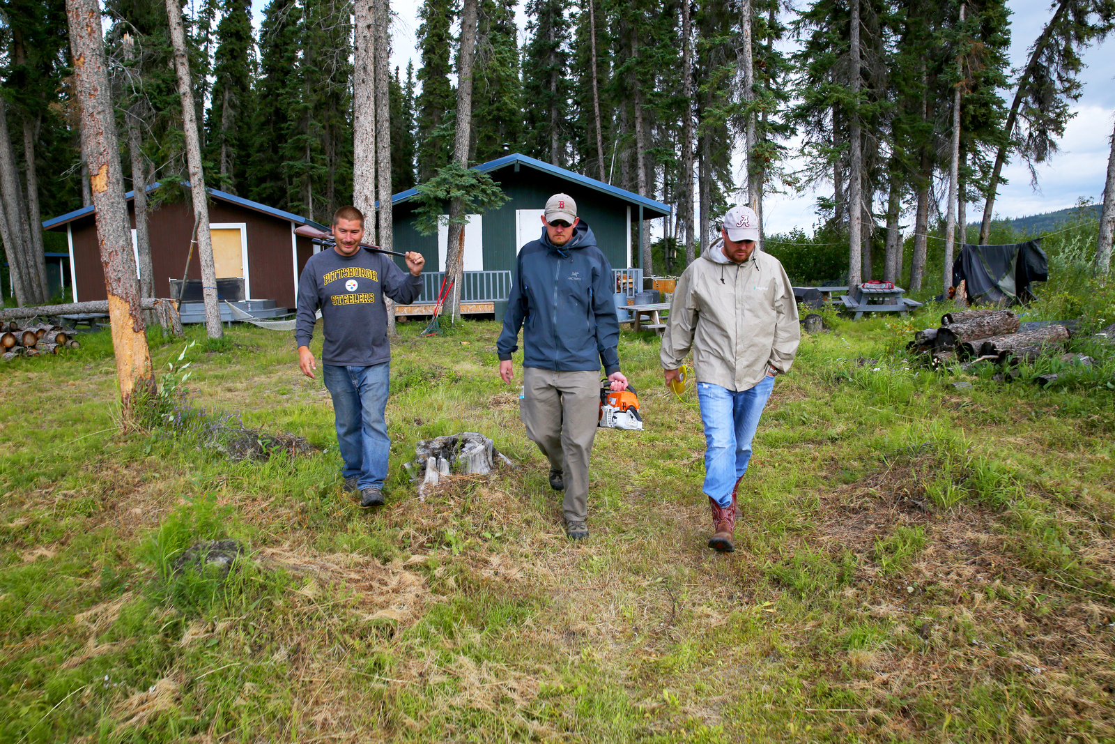 Circle, AK, July 16, 2014-- Armed with a bear gun for predators, Tanana Tribal Logistics Specialist Jack Boyle (L) and FEMA Logistics Specialists Chris Reese (C) and Brian Baker (R) retrieve chainsaws and power tools used for debris removal at this fishing camp. As subsistence hunters and fisherman, FEMA funds recovery measures at the camps damaged by severe flooding using Other Needs Assistance because this inner community depends of subsistence living for their food or sustinance. Adam DuBrowa/ FEMA