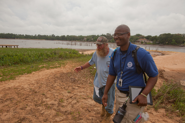 """Crescent Lake, Fla., May 10, 2014 -- FEMA Corps member David Curry takes a tour of disaster survivor, """"Catfish"""" Woodham's property in the Crescent Lake neighborhood of Pensacola. Curry is a member of FEMA's Disaster Survivor Assistance Team (DSAT) who are going door to door checking on the welfare of disaster survivors following major flash flooding along parts of the Florida Panhandle. Andrea Booher/FEMA"""