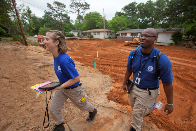 Crescent Lake, Fla., May 10, 2014 -- FEMA Corps members Stacy Kolcum and David Curry canvas the Crescent Lake neighborhood with disaster information. Kolcum and Curry are members of FEMA's Disaster Survivor Assistance Team (DSAT) who are going door to door checking on the welfare of disaster survivors following major flash flooding along parts of the Florida Panhandle. Andrea Booher/FEMA