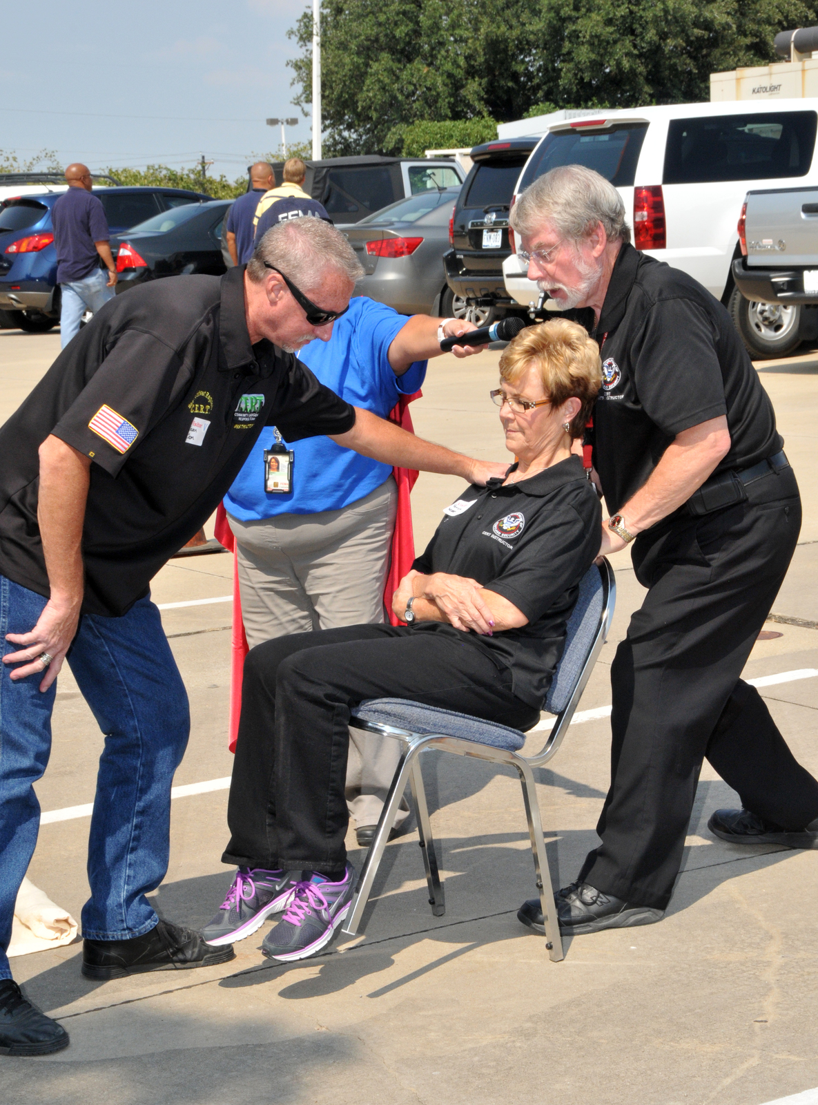 Denton, Texas, Sep. 12, 2013 -- Community Emergency Response Team (CERT) instructors Steven Clem (left) Patricia Weaver (center) and Gordy VanSteenBerg (right) demonstrate the proper technique for carrying a victim on a chair. The demonstration was part of a National Preparedness Month event held at FEMA Region VI. FEMA/Earl Armstrong