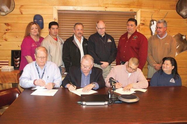 """""""Eastern Band of Cherokee Indians (EBCI) Principal Chief Michell Hicks (seated, 2nd from right) and FEMA Region 4 Administrator Phillip May (seated, 2nd from left), sign documents detailing the relationship between FEMA and the Tribe due to a recent Presidential disaster declaration for EBCI, the first in the country under the recently passed Stafford Act. Shown (left-right) seated - Michael Bolch, FEMA Federal Coordinating Offer; May; Chief Hicks; Mollie Grant, EBCI Emergency Manager; back row - Elisa Roper, FEMA Region 4 tribal liaison;  David Wachacha, EBCI Emergency Management assistant coordinator;  Eddie Huskey, EBCI Deputy Operations Officer;  Joe Stanton, North Carolina Emergency Management assistant director;  Ray Stamper, EBCI Public Safety communications manager; and Vice Chief Larry Blythe. Photo by SCOTT MCKIE B.P./One Feather """""""