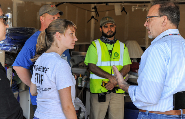 Evans, Colo., September 25, 2013 -- Rev. David Myers, Department of Homeland Security's Center for Faith-based & Neighborhood Partnerships, talks with disaster response groups Hands.org, Christian Aid Ministries, Nechama, Muslims for Humanity and AmeriCorps who joined forces to help muck out homes in Evans. Photo by Michael Rieger/FEMA