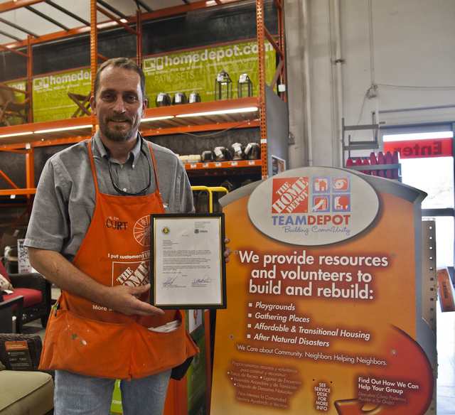 Foley, Ala., July 14, 2014 -- Curt Houchins, Home Depot Assistant Manager, holds a Certficate of Appreciation given to the Foley, Ala. Home Depot by the FEMA Mitigation division for its assistance in providing FEMA with space in their store so that Mitigation and Individual Assistance specialists could provide residents with information they could use following the tornadoes and severe storms that swept through the area in early May. Patsy Lynch/FEMA