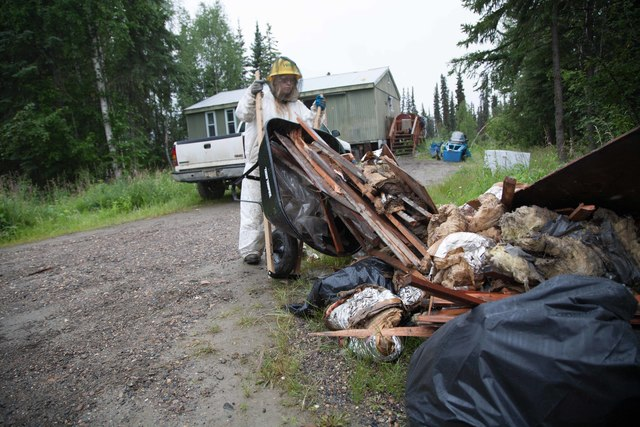 """Galena, Alaska, July 24, 2013 -- An AmeriCorps member, complete with hard hat, hazardous materials suit, mosquito net and gloves empties a wheelbarrow of house debris onto the street for pickup by the village. """"HazMat"""" suits and related safety gear are required safety gear. Photo by  Ed Edahl/FEMA"""