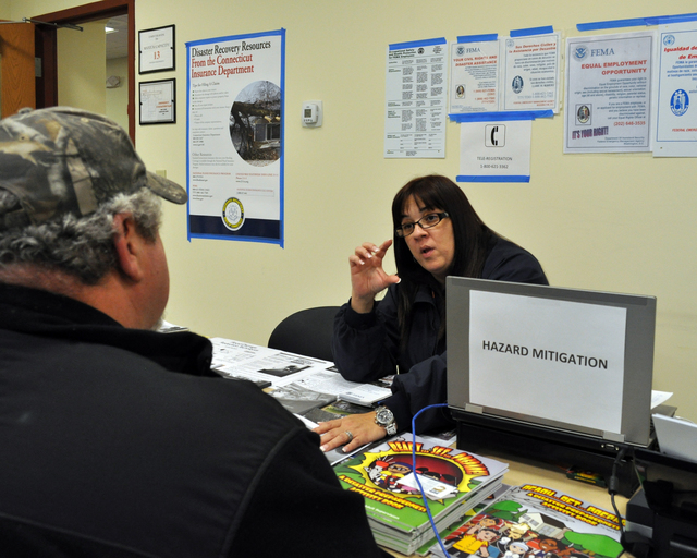 Greenwich, Conn., Dec. 4, 2012 -- Nellie Anne Batiz Perez, Hazard Mitigation Specialist, explains proper mixing proportions to Sandy survivor Nick Lombardi at the Greenwich Disaster Recovery Center.  FEMA's Disaster Recovery Centers are staffed with representatives from Individual Assistance, Hazard Mitigation and the Small Business Administration.  Photo by Marilee Caliendo/FEMA