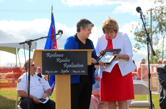 Joplin, Mo., May 22, 2013 -- U.S. Department of Homeland Security Secretary Janet Napolitano presents the Rick Rescorla National Award for Resilience to Jane Cage and the citizens of Joplin at the community's 2-year tornado anniversary ceremony. Cage heads the Joplin Area Citizens Advisory Recovery Team, a citizen-based group that was begun with the help of FEMA after the city was devastated by an EF 5 tornado in May 2011 to help guide the community's long-term recovery. Rescorla died on 9/11 after helping to save scores of Morgan Stanley employees from one of the World Trade Center towers.  This is the first national presentation of the DHS award in his honor. Seated in the background from left:  Joplin Fire Chief Mitch Randles and Missouri Gov. Jay Nixon.  Barb Sturner/FEMA