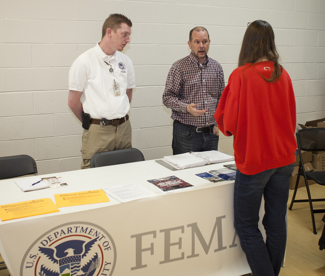 Lisle, Ill., June 8, 2013 -- FEMA Assistant External Affairs Officer for Private Sector Chad McCormick and Illinois Flood Plain Program Coordinator Brian Eber answer questions at the FEMA booth during the Flood Expo designed to help residents learn about flood repair options and floodplain ordinances in the Village of Lisle following the wide spread flooding as a result of severe storms and straight-line winds during April and May 2013.  David Fine/FEMA