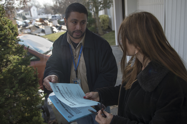 Long Beach, N.Y., Nov. 10, 2012 -- Transportation Security Administration representative Louis Quinones informs Hurricane Sandy survivor and Long Beach, N.Y. resident Anne-Marie Frisco of how to take advantage of FEMA's services. FEMA, Border Patrol, TSA and ICE visited homes to inform residents of FEMA services as part of the Federal Surge Crisis Response