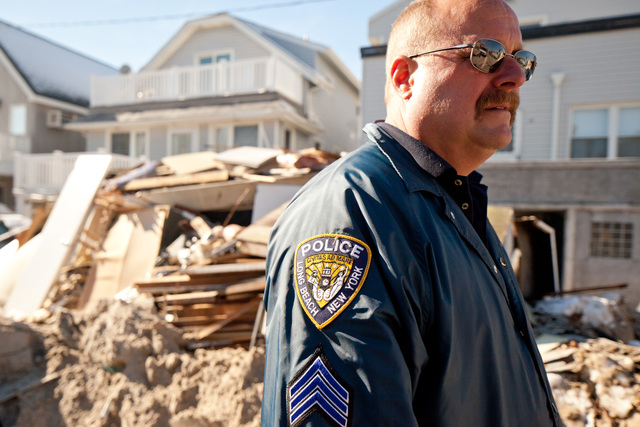 Long Beach, N.Y., Nov. 9, 2012 -- Long Beach Police Sgt. Eric Creegen views damage in his community caused by Hurricane Sandy. The area received several feet of surge from the storm and created widespread flooding, power outages and devastation on Long Beach, New York. FEMA is working with many partners including federal, state, local and tribal governments, voluntary, faith-based and community-based organizations, and the private sector to assist residents impacted by Hurricane Sandy. Andrea Booher/FEMA