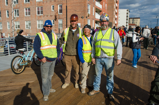 Long Beach, N.Y., October 25, 2013 -- A few days before the one year anniversary of Hurricane Sandy, local officials cut the ribbon to open the completed boardwalk to the public. Seventy-five percent of the cost to rebuild the boardwalk was funded by the Federal Emergency Management Agency's Public Assistance program and New York State will cover the remaining cost. Some of the workers who built the boardwalk were on hand for the ceremony. From left to right, Matt Laub , Ned Quane, Byron Holland, and Mike O'Connor. K.C.Wilsey/FEMA