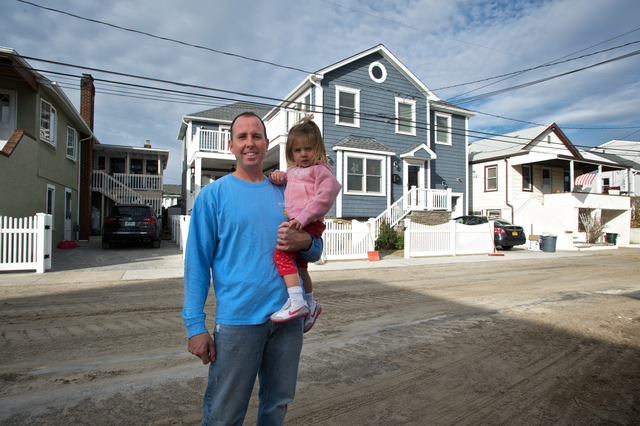 Long Island, N.Y., Nov. 16, 2012 -- Tomas O'Grady, pictured with his daughter, is satisfied with the construction of his home, which was built before Hurricane Sandy. After the hurricane, most of the houses around his were damaged due to the floods but his house remained intact due to his following the state building requirements. Mitigation success stories help home owners understand how to construct or improve construction to prevent damages in any future disaster event. Eliud Echevarria / FEMA