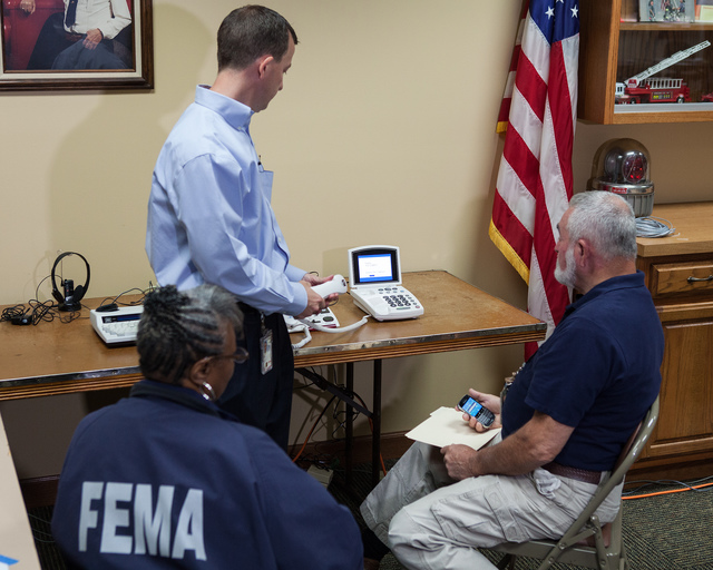 Marseilles, Ill., May 24, 2013 -- FEMA Disability Integration Advisor David Svir makes a test call using the CapTel captioning service to the Blackberry of FEMA Disaster Recovery Center Manager Paul Buffington and FEMA Applicant Specialist Roberta Washington during a training session on the proper use of various visual and auditory aids available inside the DRC to assist people with hearing, visual and language barriers. Disaster Recovery Centers are open across the state of Illinois assisting survivors following the severe storms, straightline winds and flooding that caused damage to thousands of homes in April and May 2013.  David Fine/FEMA