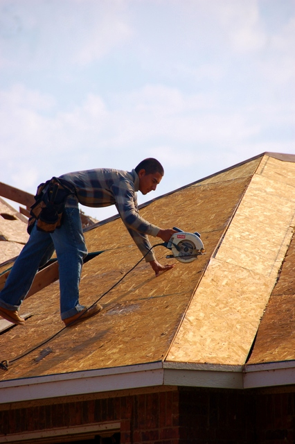 Moore, Okla., July 29, 2013 -- A roofers works to repair a home that was damaged in the May 20th EF-5 tornado. Roof damage is of the most common forms of damage seen sustained by homes still standing. Dominick Biocchi/FEMA