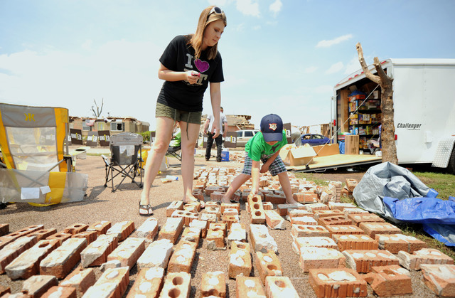 Moore, Okla., June 5, 2013 -- Plaza Towers Elementary School first grade teacher Sarah Tauscher, left, and her son Jackson Kirksey, pick out a brick from the school so that they can take part in a personal art project.  The project called {HOPE} raisers is a group of individuals, businesses and causes that care about the community from all over the country. Together they use their time, talent and treasures to create community engagement and Raise Some Hope.  Jocelyn Augustino/FEMA