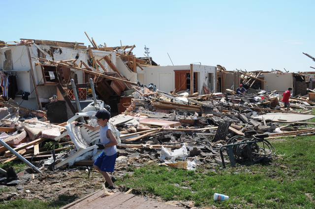 Moore, Okla., May 22, 2013 -- A child collects possessions scattered by the deadly May 20 tornado.  President Obama signed an expedited Presidential Disaster Declaration on May 21 and FEMA is here to provide recovery services for eligible storm survivors. George Armstrong/FEMA
