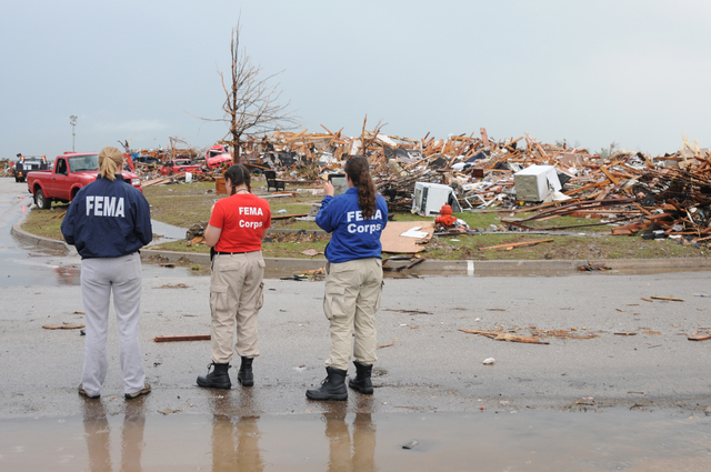 Moore, Okla., May 23, 2013 -- FEMA Corps Disaster Survivor Assistance Team (DSAT) members Brittany Bieler, Jamie Flynn, and FEMA Corps Branch Chief Deanne Criswell look for survivors in this neighborhood which was extensively damaged by the deadly May 20 tornado. DSAT can provide recovery information and actually register survivors on-site for FEMA assistance. George Armstrong/FEMA