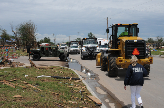 Moore, Okla., May 23, 2013 -- On Santa Fe Avenue, FEMA Public Information Officer Susan Solomon walks by state transportation vehicles involved in debris removal and miliary personnel providing security in this area affected by the deadly May 20 tornado. FEMA may reimburse the state for debris removal expenses under Category A, Public Assistance. George Armstrong/FEMA