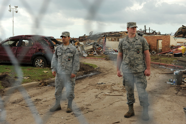 Moore, Okla., May 25, 2013 -- Airmen First Class Perez, left and Forbes from the Oklahoma Air Guard stand watch at Plaza Towers Elementary School which has been fenced off after being damaged by the recent tornado on May 20, 2013.  President Obama will visit the area on May 26, 2013.  Jocelyn Augustino/FEMA