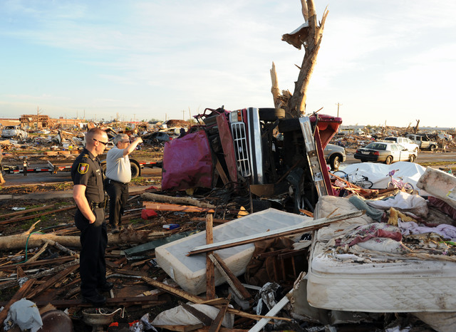 Moore, Okla., May 25, 2013 -- Moore Emergency Manager Gayland Kitch, right and Officer Eric Thomas survey the damage where Thomas' home once stood prior to the recent tornado.  Residents impacted by the recent tornado are encouraged to register with FEMA for assistance.  Jocelyn Augustino/FEMA