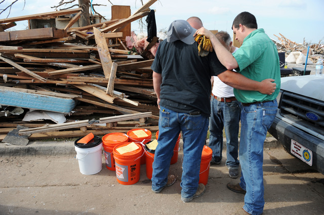 """Moore, Okla., May 25, 2013 -- Volunteer Justin Murphy, left, of Southern Baptist Convention prays with local residents impacted by the tornado.  Murphy was delivering """"buckets of love"""" which include cleanup and first aid items.  Jocelyn Augustino/FEMA"""