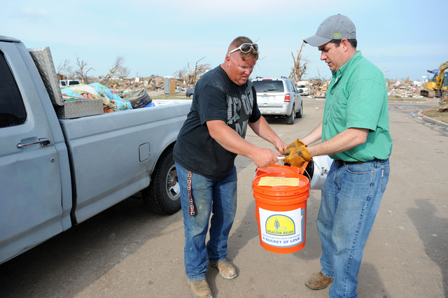 """Moore, Okla., May 25, 2013 -- Volunteer Justin Murphy, right, of Southern Baptist Convention drops off supplies to Jack Richey. Local residents impacted by the tornado. Murphy was delivering """"buckets of love"""" which include cleanup and first aid items.  Jocelyn Augustino/FEMA"""