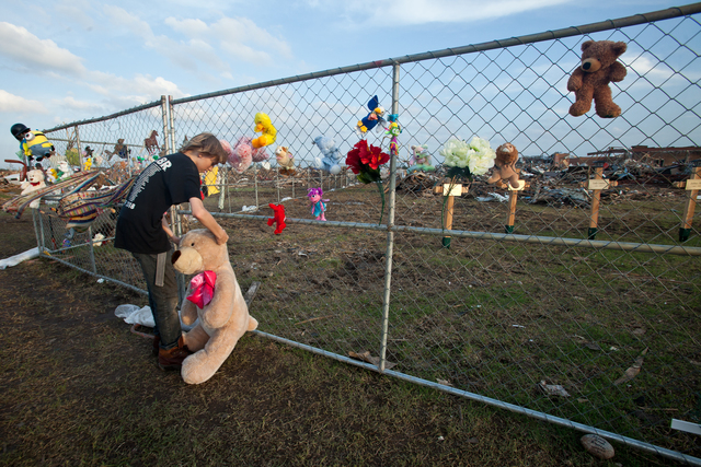 Moore, Okla., May 26, 2013 -- Moore resident, Brandon Harris  leaves a Teddy Bear at the impromptu memorial shrine at Plaza Towers Elementary School The Moore area was struck by a F5 tornado on May 20, 2013. Andrea Booher/FEMA
