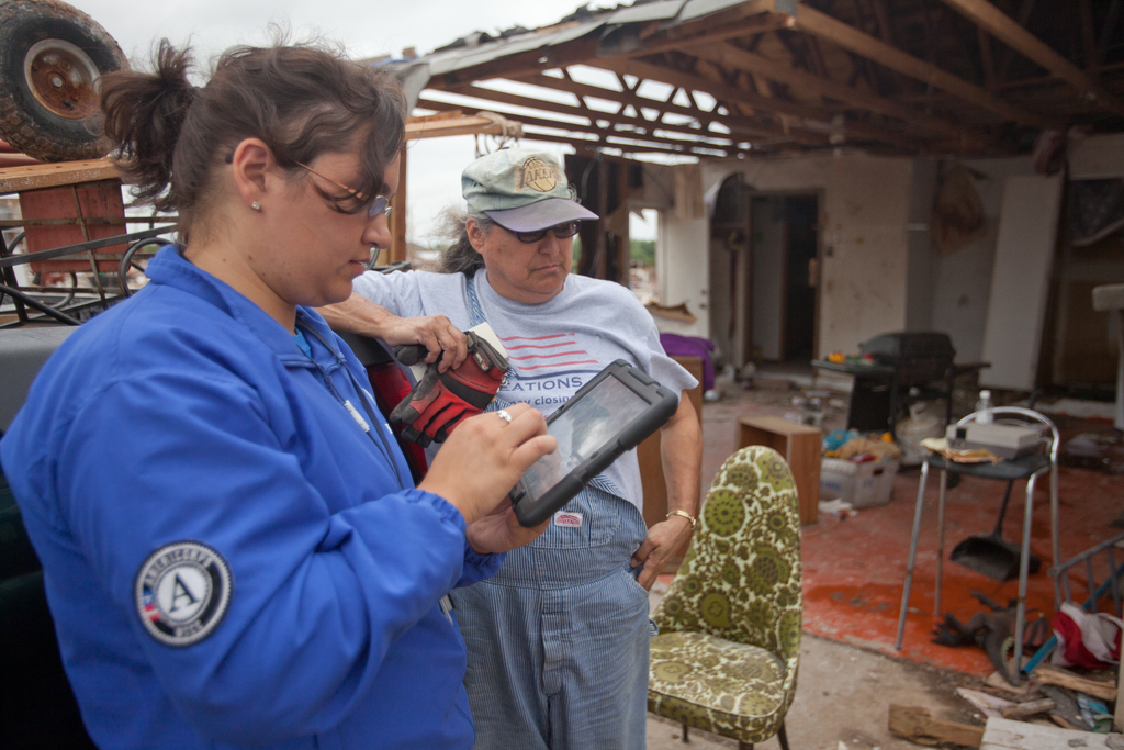 Moore, Okla., May 27, 2013 -- FEMA Corps member, Ana Canizales registers disaster survivor, Sue Kemp for disaster assistance. The Whispering Oaks area of Moore was struck by a F5 tornado on May 20, 2013. Andrea Booher/FEMA