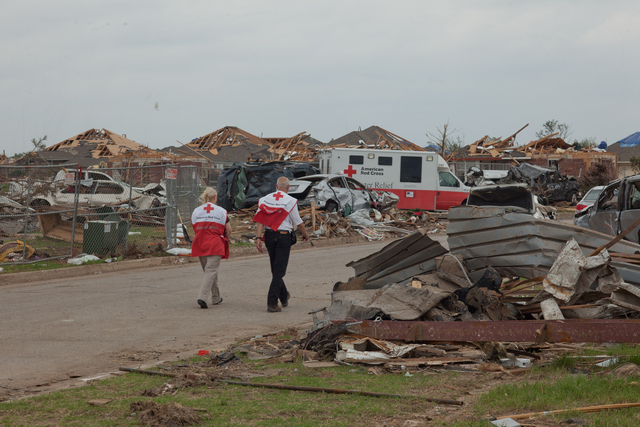 Moore, Okla., May 29, 2013 -- American Red Cross volunteers, Adriana Persenaire and Dr. Alan Krohn walk through Westmoore neighborhood providing counseling to tornado survivors. The Moore area was struck by a F5 tornado on May 20, 2013. Andrea Booher/FEMA