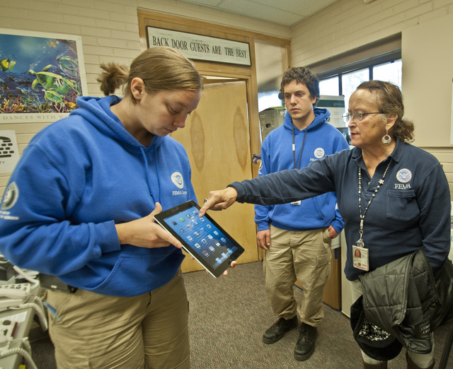 Nederland, Colo., October 16,2013 -- Karen Bogenberger, FEMA Corps Disability Communications Specialist, demonstrates an iPhone application (app) which can be used by a hearing impaired or voice disabled individual to a FEMA Individual Specialist at a Disaster Recovery Center in Nederland, Colo.  FEMA provides a variety of services to insure that all residents are able to register and to get information they need to assist with their recovery from recent flooding. FEMA is working with local, state and other federal agencies to assist residents in Colorado who were affected by flooding.  Photo by Patsy Lynch/FEMA