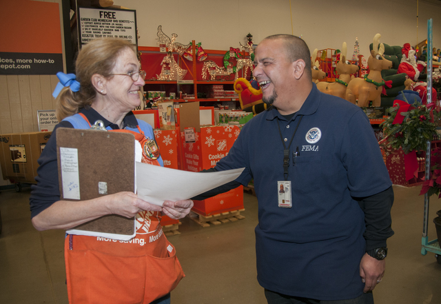 Neptune, N.J., Dec. 10, 2012 -- Jose Gonzaga, FEMA Mitigation specialist, shares a laugh with a Home Depot employee who is also a Hurricane Sandy survivor at a Home Depot in Neptune, NJ.  FEMA has arranged for mitigation specialists to set up information booths in various home improvement stores to assist residents affected by Hurricane Sandy to get information that they can use during their recovery. Photo by Patsy Lynch/FEMA