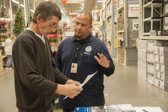 Neptune, N.J., Dec. 10, 2012 -- Jose Gonzaga, FEMA Mitigation specialist, talks to a Hurricane Sandy survivor at a Home Depot in Neptune, NJ.  FEMA has arranged for mitigation specialists to set up information booths in various home improvement stores to assist residents affected by Hurricane Sandy to get information that they can use during their recovery. Photo by Patsy Lynch/FEMA