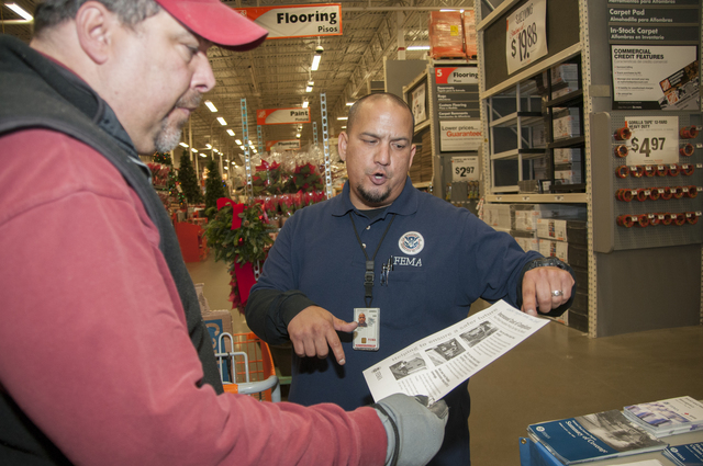 Neptune, N.J., Dec. 10, 2012 --Jose Gonzaga, FEMA Mitigation specialist, talks to a Hurricane Sandy survivor at a Home Depot in Neptune, NJ.  FEMA has arranged for mitigation specialists to set up information booths in various home improvement stores to assist residents affected by Hurricane Sandy to get information that they can use during their recovery. Photo by Patsy Lynch/FEMA
