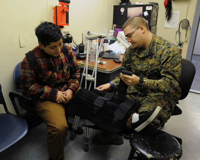 New York, N.Y., Dec. 1, 2012 -- FEMA Corps member Wiley Cruz, left, gets her legged examined by Louis Barquin, medic, HM3, aboard the Training Ship Empire State VI, docked on the East River at the foot of the Throgs Neck Bridge.  The ship has been used for accommodations for volunteers who have come to help with recovery efforts to Hurricane Sandy.  Jocelyn Augustino/FEMA