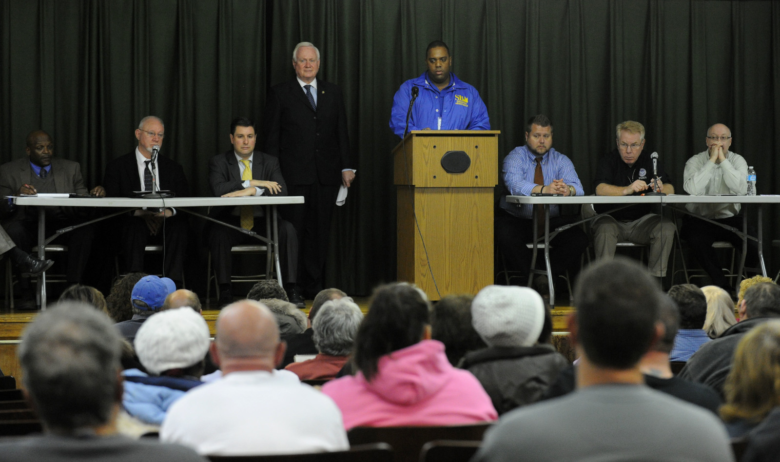 New York, N.Y., Dec. 11, 2012 --Small Business Administration (SBA) Public Affairs Specialist Andre Ledgister, at podium, answers questions from the audience regarding SBA loans.  A town hall meeting was held with local, state and federal officials at public school 277, to discuss issues surrounding the Gerritson Beach community.  Residents who have not yet applied for assistance and were impacted by Hurricane Sandy are encouraged to apply for assistance.  Jocelyn Augustino/FEMA