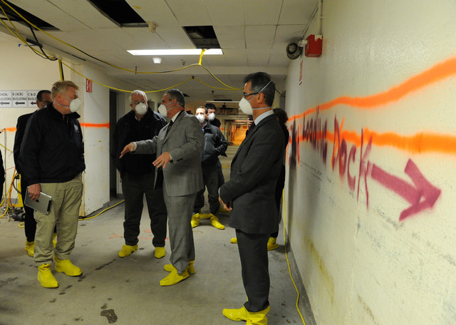 New York, N.Y., Dec. 14, 2012 -- Bellevue Hospital Associate Executive Director of Facilities Management, Michael Rawlings, center, explains the damage incurred by Hurricane Sandy to Administrator Craig Fugate, second from left, and FEMA Federal Coordinating Officer Michael Byrne, left. The orange line on the wall indicates how high the flood waters were after Hurricane Sandy.  Due to the continuing efforts of abatement, visitors are required to wear a face mask and rubber boots.  Jocelyn Augustino/FEMA