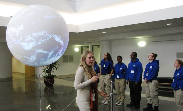 """Norman, Okla., November 7, 2013 -- Members of FEMA Corps Team Hickory 3 viewing the National Weather Center's (NWC) 'Science on a Sphere' during a tour of the center's campus in Norman, Oklahoma. Nicole Robertson, Program Manager at the NWC's Office of Weather Programs & Projects, explains the sphere is a global display system that uses computers and video projectors to display looped, animated images of atmospheric storms, climate change, and ocean temperature onto the six foot diameter sphere. The previous 30 days of the world's weather, including Super Typhoon Haiyan as it formed and later approached the Philippines, was being shown on the day of Hickory 3's visit."""
