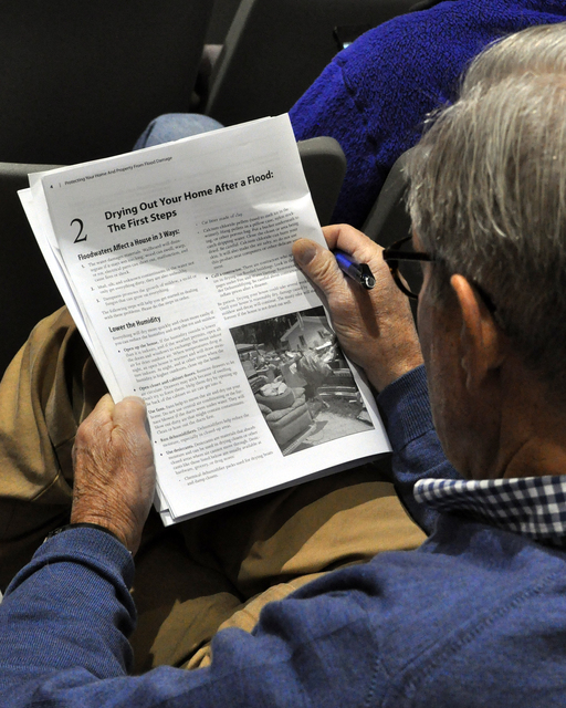 Norwalk, Conn., Dec. 1, 2012 -- This disaster survivor puts his time awaiting the start of the meeting to good use, reading FEMA handout material. Congressman Jim Himes sponsored this Town Hall Meeting where representatives of FEMA and the Small Business Administration, outlined the services they offer to those affected by the hurricane.   Photo by Marilee Caliendo/FEMA