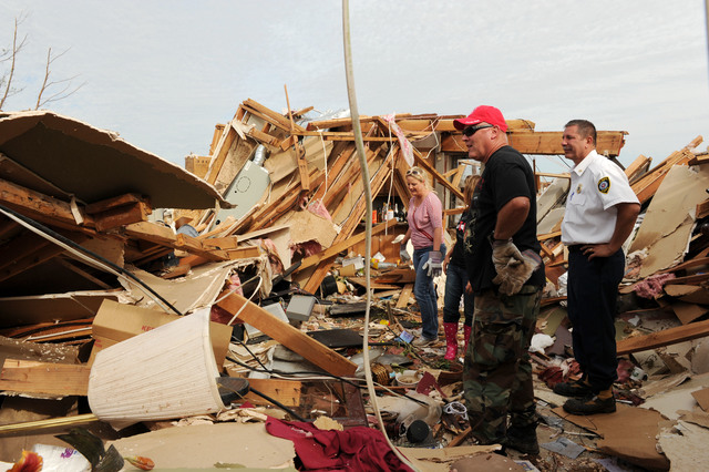 Oklahoma City, Okla., May 23, 2013 -- Local firefighter Jon Cook, black shirt, stands in what remains of his living room with Chief Cecil Clay, white shirt, and his girlfriend Dusti Talkington, far left.  Jocelyn Augustino/FEMA