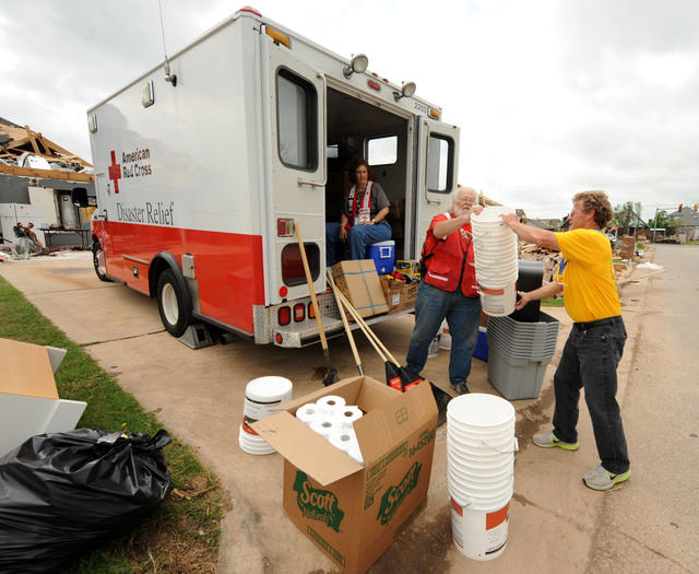 Oklahoma City, Okla., May 31, 2013 -- American Red Cross volunteer Mike Lyons, center,  hands out work supplies to Southern Baptist Convention volunteer Terry Myers, right.  The Red Cross has supplies to help residents with cleanup.  Jocelyn Augustino/FEMA